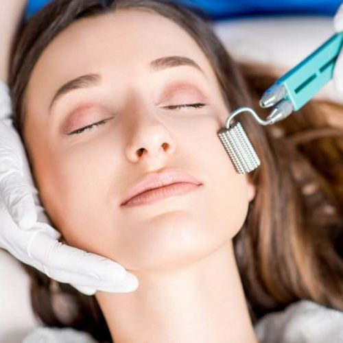 Making dry needlying procedure on woman's face in the cosmetology office